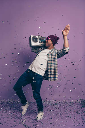 Vertical full length size body photo portrait of crazy cheerful handsome nice positive glad moving having free time carefree student enjoying loud volume isolated violet glitter background