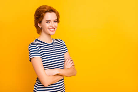Close up side profile photo beautiful self-confident she her lady hands arms crossed positively toothy beaming smile wear casual striped white t-shirt outfit clothes isolated yellow bright background