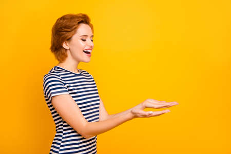 Close-up zijprofielfoto mooi zij haar dame handen armen palmen lege ruimte met nieuw product opgewonden slijtage casual gestreepte witte t-shirt outfit kleding geïsoleerd gele heldere achtergrond