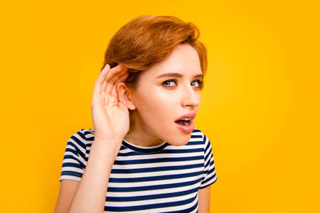 Close up photo beautiful amazing she her lady hand arm raised to ear listening romours chatterbox bad person wearing casual striped white blue t-shirt outfit clothes isolated yellow bright background Stockfoto
