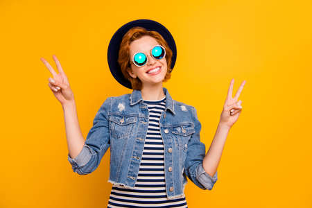 Close up photo beautiful she her lady arm hand traveler perfect modern look show v-sign say hi wear specs vintage hat casual striped t-shirt jacket jeans denim isolated yellow bright vivid background