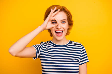 Close up photo beautiful amazing she her lady funky okey symbol near eye watch see look new product wearing casual striped white blue t-shirt outfit clothes isolated yellow bright vibrant background