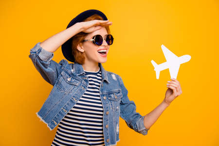 Close up photo beautiful she her lady arm hand paper airplane traveler look far away distant view wear specs vintage hat casual striped t-shirt jacket jeans denim isolated yellow bright background