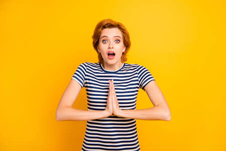Close up photo beautiful amazing she her lady eyes closed hands arms together asking assistance praying wear casual striped white blue t-shirt outfit clothes isolated yellow bright vivid background Imagens