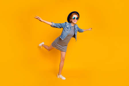 Full length body size view portrait of nice pretty lovely charming attractive cheerful cheery optimistic girl flying on air like plane free time isolated over bright vivid shine yellow background 写真素材