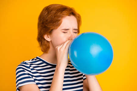 Close-up portrait of nice charming attractive girlish childish lady blowing blue baloon festal event celebratory day preparation tradition isolated over bright vivid shine yellow background