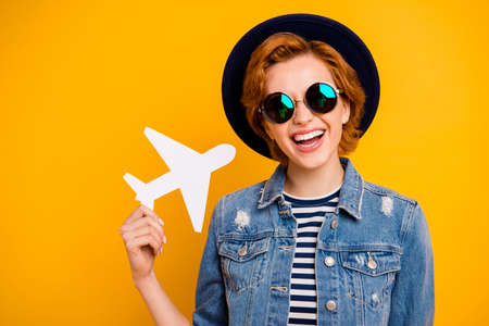 Close up photo beautiful amazing she her lady hand arm little small airplane traveler wear specs vintage hat casual striped t-shirt jacket jeans denim outfit isolated yellow bright vivid background