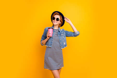 Close up photo beautiful foxy she her lady traveler modern look hand arm pink coffee container hold vintage hat wear specs casual striped t-shirt dress jeans denim isolated yellow bright background