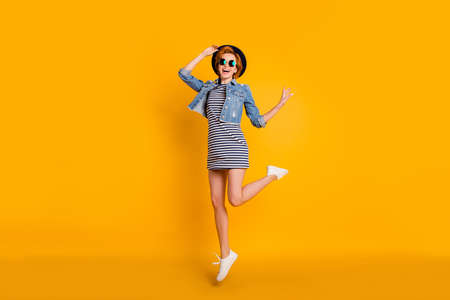 Full length body size photo foxy she her chic lady jumping high sunny day off fine weather weekend wear specs vintage hat casual striped t-shirt dress jeans denim isolated yellow bright background
