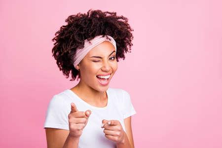 Gros plan photo belle incroyable drôle elle sa peau foncée yeux clignotants positifs amical indiquant les doigts votre tour c'est vous symbole porter un foulard décontracté t-shirt blanc isolé rose fond clair