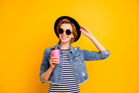 Close up photo beautiful she her lady traveler modern perfect look hand arm pink coffee container wear specs vintage hat casual striped t-shirt jacket jeans denim isolated yellow background Stock fotó
