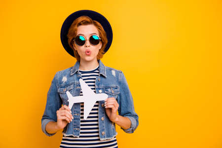 Close up photo beautiful foxy she her lady arm hand paper airplane traveler not expect low price wear specs vintage hat casual striped t-shirt jacket jeans denim isolated yellow bright background Stock fotó