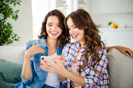 Close up photo beautiful ladies fellows buddies laughter telephone hands arms show screen funky joke picture wear casual jeans denim checkered plaid shirts apartments sit divan couch indoors.