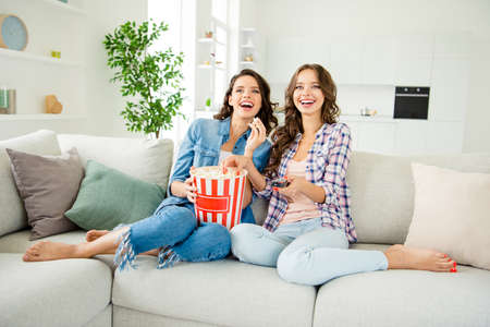 Close up photo beautiful funky ladies hold large corns container change channels favorite show laughter wear casual jeans denim checkered plaid shirts apartments sit divan room indoors.