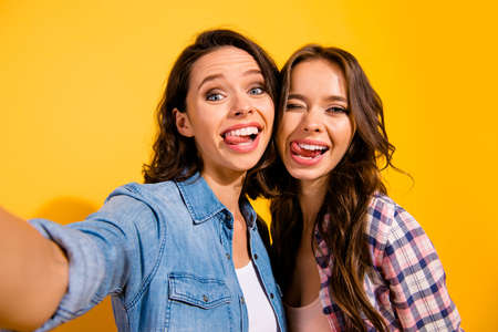 Close up photo funny carefree careless childish playful fellows take photo beautiful excited fool travel summer content enjoy positive cheerful satisfied isolated checked jeans shirt yellow background
