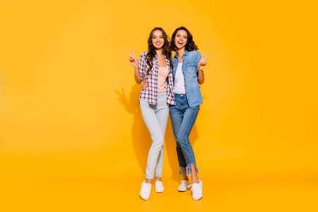 Full length body size view photo of charming cute fellows ladies friendly person free time make v-signs excited enjoy weekends summer isolated have denim plaid clothing on yellow background