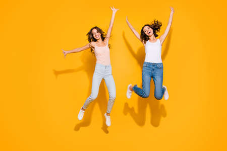 Full length body size view photo charming ladies weekends free time holidays satisfied laugh laughter glad content funny funky summer travel long hair plaid clothes jeans isolated yellow background 写真素材 - 121957936