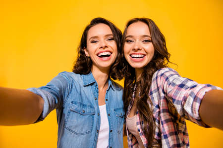 Close up photo nice charming ladies make photos unforgettable moments summer free time holidays weekends feel satisfied content glad wear fashionable clothes long hair isolated yellow background