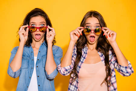 Close up photo charming funny hipsters person astonished impressed incredible information bargain news summer travel touch modern specs open mouth checked shirts denim isolated yellow background Banco de Imagens