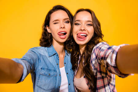 Close up photo funny carefree careless childish playful teen fool make photos travel summer beautiful excited enjoy positive cheerful satisfied content  isolated checked jeans shirts yellow background