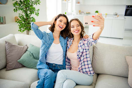 Close up photo beautiful she her ladies best buddies laugh laughter make take selfies telephone hand arm coquette wear casual jeans denim checkered plaid shirts apartments sit divan couch indoors