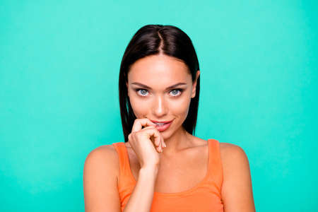 Close up photo portrait of flirty nice positive with perfect smooth flawless healthy skin she her lady biting lips holding finger forefinger near mouth isolated pastel background