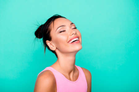 Close up side profile photo beautiful she her lady trendy stylish hairdo toothy ideal appearance eyes closed overjoyed laugh wear casual pink tank-top outfit clothes isolated teal turquoise background