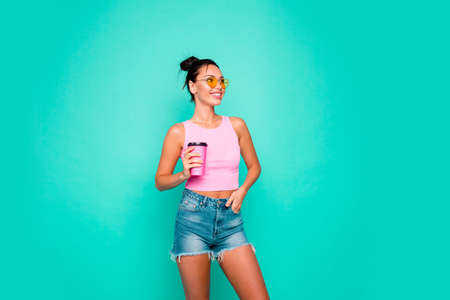 Close up photo beautiful she her lady funny hairdo hold hand arm takeaway coffee look empty space interested curious wear casual pink tank-top jeans denim shorts isolated teal turquoise background Stock Photo