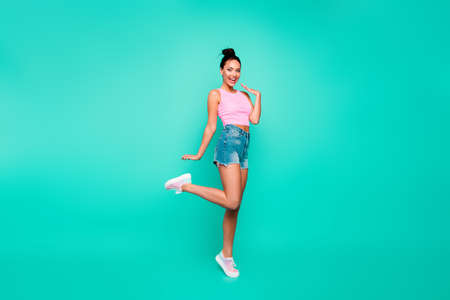 Full length side profile body size photo beautiful she her lady stylish hairstyle have walk park weekend wear casual pink tank-top jeans denim shorts outfit clothes isolated teal turquoise background Stock Photo