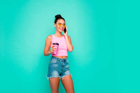 Close up photo beautiful she her lady funny hairdo hold hand arm takeaway beverage interested curious telephone speak tell wear casual tank-top jeans denim shorts isolated teal turquoise background Stock Photo