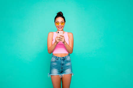 Close up photo beautiful funky hairstyle she her lady hold hands arms telephone reader sale discount shopping notification wear casual tank-top jeans denim shorts isolated teal turquoise background Stock Photo