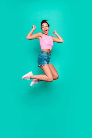 Verticale volledige lengte zijprofiel lichaamsgrootte foto mooi zij haar grappig schreeuwen trendy kapsel springen hoog geluk loterij slijtage casual roze tank-top jeans denim shorts geïsoleerd groenblauw turkooizen achtergrond