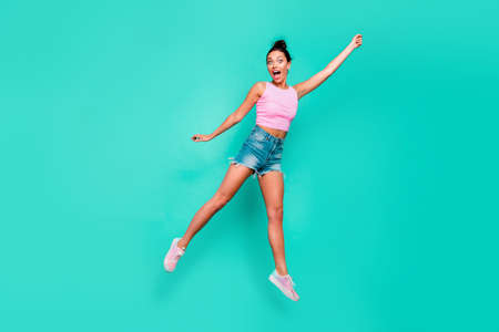Full length body size photo beautiful she her jump high trendy stylish hairdo pretend merry umbrella flight not believe wear casual pink tank-top jeans denim shorts isolated teal turquoise background