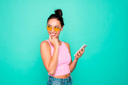 Close up side profile photo beautiful funky hairstyle she her lady hold hands arms telephone look wondered empty space think wear specs casual tank-top isolated bright teal turquoise background