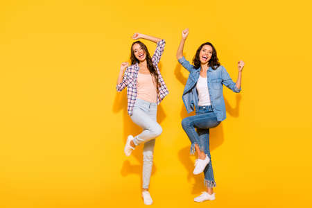 Full length body size view photo amazed charming satisfied cute ladies raise fists scream glad enjoy rejoice ecstatic travel summer yeah lucky luck checked shirts long hair isolated yellow background