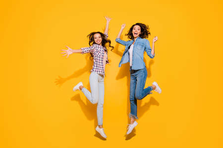 Full length body size view photo cute funny funky person beautiful free time weekends holidays travel spring summer raise hands arms fists long hair fool plaid modern outfit isolated yellow background Stock Photo