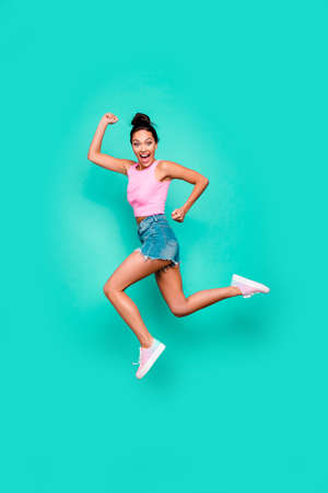 Vertical full length body size photo beautiful she her stylish trendy hairdo jump high win winner victory achievement wear casual pink tank-top jeans denim shorts isolated teal turquoise background