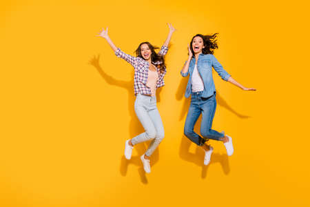 Full length body size view photo lovely fellows fellowship satisfied glad free time weekends travel beautiful spring summer raise hands arms scream shout checked shirt isolated yellow background Stock Photo