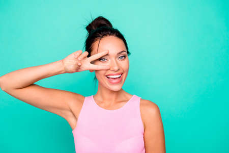 Close up photo beautiful amazing she her lady stylish hairstyle ideal appearance show v-sign near eye say hi friends relatives wear casual pink tank-top clothes isolated teal turquoise background