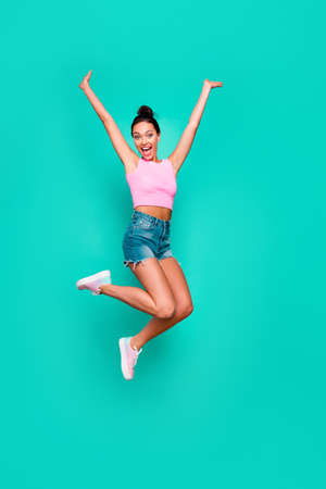 Vertical full length body size photo beautiful she her stylish trendy hairdo jump high unexpected lucky achievement wear casual pink tank-top jeans denim shorts isolated teal turquoise background