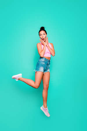 Vertical full length body size photo beautiful she her stylish trendy hairdo jump high unexpected lucky goal lottery wear casual pink tank-top jeans denim shorts isolated teal turquoise background Stock Photo