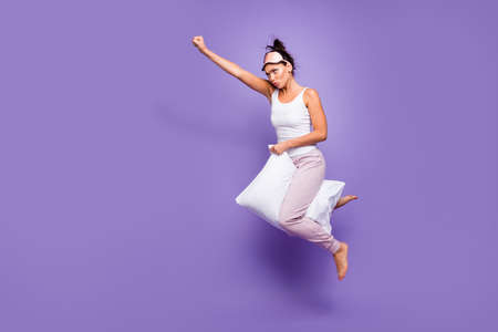 Full length side profile body size photo beautiful she her lady super power flight hold between legs pillow funny satisfied wear sleeping mask pants tank-top pajamas isolated violet purple background Фото со стока
