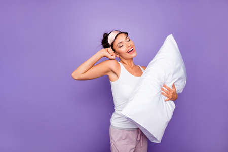 Close up side profile photo beautiful she her lady hold hug arms hands pillow satisfied refreshed yawn just woke up wear sleeping mask white tank-top pajamas isolated violet purple background Stock Photo