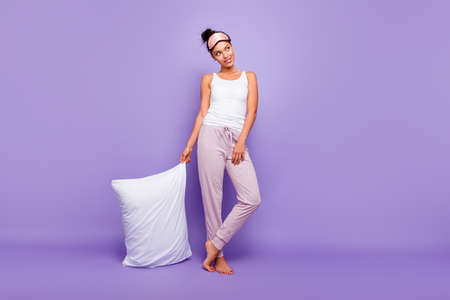 Full length body size photo beautiful she her lady look empty space wondered thoughtful hold hand arm pillow barefoot wear sleeping mask pants tank-top pajamas isolated violet purple background Stock Photo