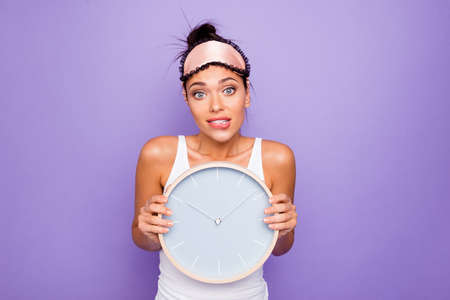 Close up photo beautiful she her lady hold arms hands round circle wall watch ten oclock  just woke up miss work oh no bite lip wear sleeping mask white tank-top isolated violet purple background Stock Photo