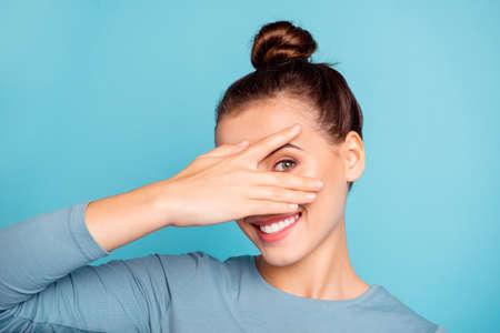 Primo piano foto bella lei la sua signora braccio mano dita sollevate nascondi metà faccia toothy raggiante sorriso carino simpatico amichevole godere giorno libero indossare maglione casual pullover isolato blu sfondo luminoso