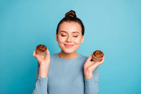 Close up photo beautiful she her lady advising buy buyer try new yummy just baked tasty cacao color muffins dreamy close eyes nice smell wear casual sweater pullover isolated blue bright background