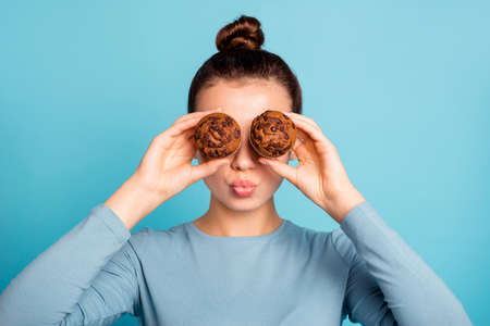 Close up photo beautiful she her lady send air kiss hide eyes advising buy buyer try new yummy just baked tasty cacao color muffins wear casual sweater pullover isolated blue bright background
