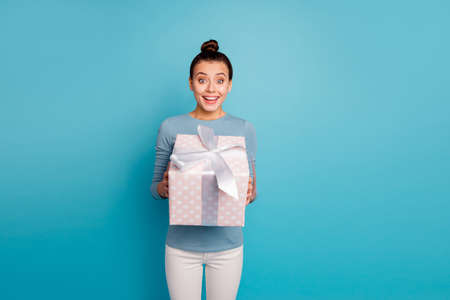 Portrait of cute astonished teen teenager get incredible package for 14-february 8-march impressed wonder expression holiday wear fashionable outfit white trousers isolated on blue background 写真素材