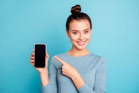 Nahaufnahmeporträt von ihr hübsch aussehendes, attraktives, süßes, fröhliches Teenager-Mädchen, das in der Hand eine neue coole Kaufanzeige hält, einzeln auf hell leuchtendem türkisfarbenem Hintergrund Standard-Bild